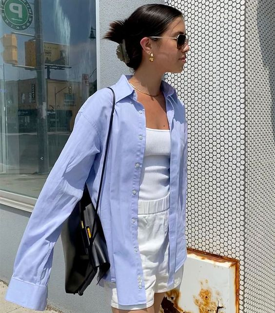 a summer outfit with a white top and shorts, an oversized blue shirt over them and a black bag
