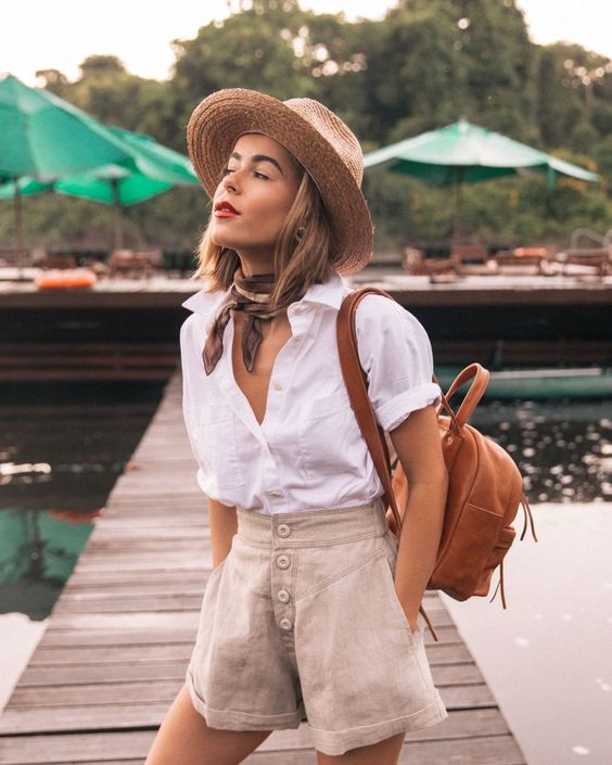 a summer vacation look with a white linen shirt, neutral high waisted Bermudas, a hat, a neck tie and a brown backpack