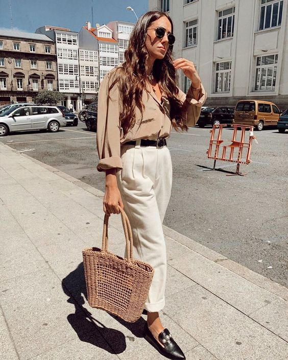 a summer work look with a tan linen shirt, white trousers, black moccasins and a brown woven bag