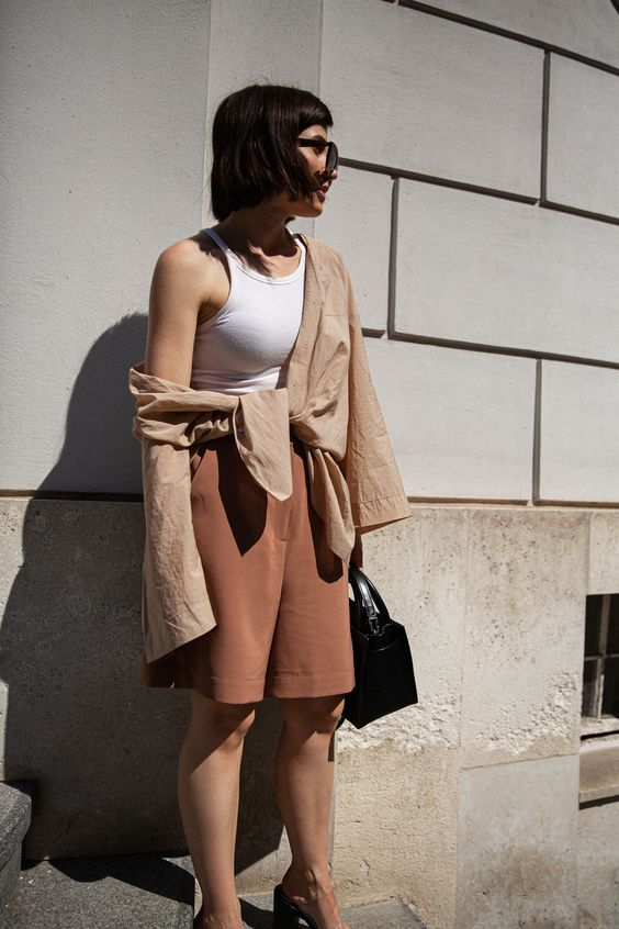 a summer work outfit with a white halter neckline top, a tan linen shirt and rust-colored linen shorts plus a black bag