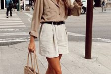 a tan linen shirt, white linen shorts and a black belt, woven flats and a straw tote for a hot working day