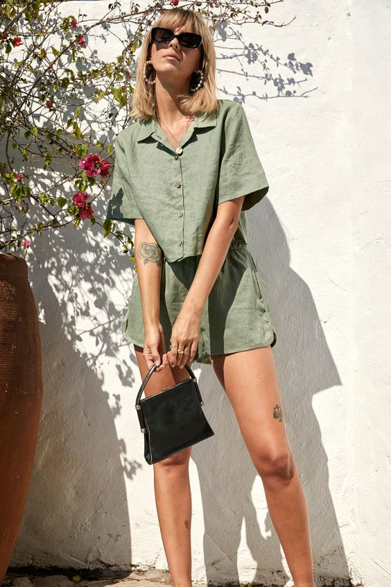 a trendy outfit with a green linen cropped shirt and shorts, slippers and a navy bag is ideal for this summer
