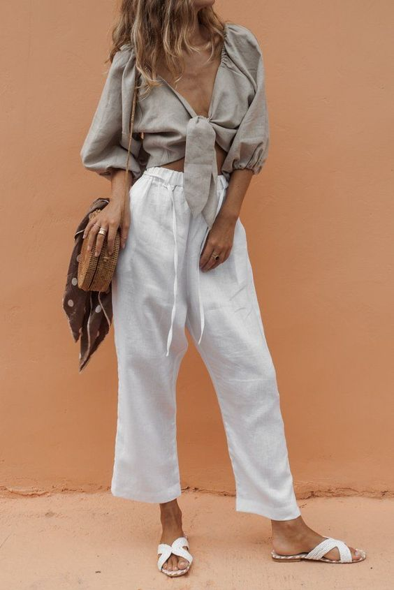 a vacation look with a grey tied up cropped blouse with puff sleeves, white cropped pants, white slippers and a woven bag