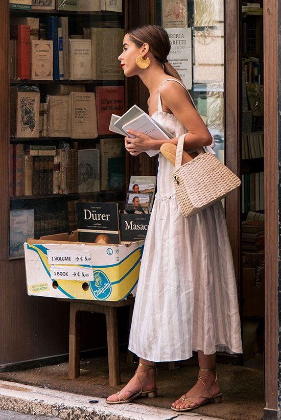 a vacation look with a striped grey and white sundress and thick straps, metallic kitten heels and a white straw bag