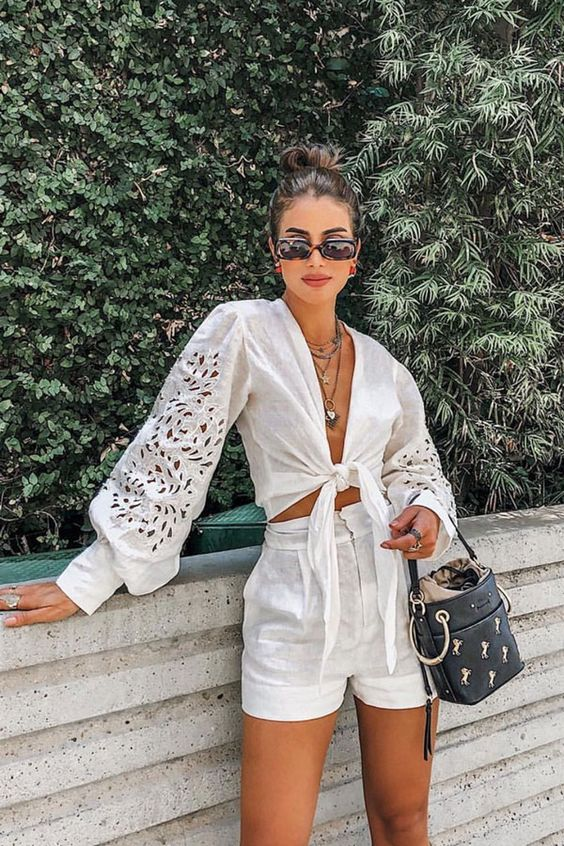 a vacation look with a white linen crop blouse with puff sleeves, high waisted linen shorts and a black bucket bag