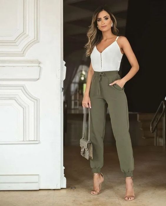 a white button up spaghetti strap top, olive green pants, nude heels and a neutral printed bag