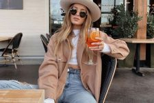 a white crop top, a tan jacket, blue denim shorts, white sneakers, a neutral hat for a casual summer look