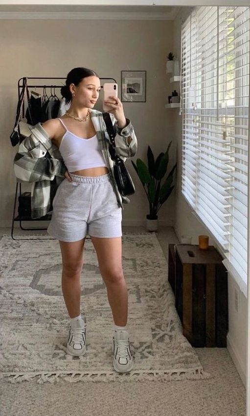 a white crop top, grey shorts, a plaid flannel shirt and grey trainers plus a black bag
