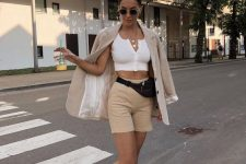 a white crop top with buttons, tan shorts, a tan oversized blazer, white trainers and a waist bag