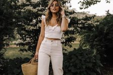 a white crop top with ruffle straps, white jeans, white strappy shoes and a straw tote