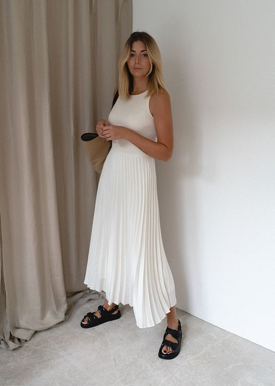 a white halter neckline top, a white pleated midi skirt, black dad sandals and a tan tote for a breezy summer work look