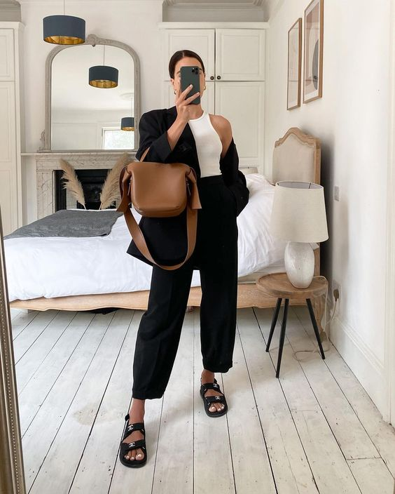 a white halter neckline top, black high waisted trousers, black dad sandals, a black oversized blazer and a brown bag for an elegant work look