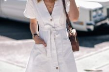 a white linen button up mini dress with a V-neckline and pockets, a hat, a brown round bag and a neck tie