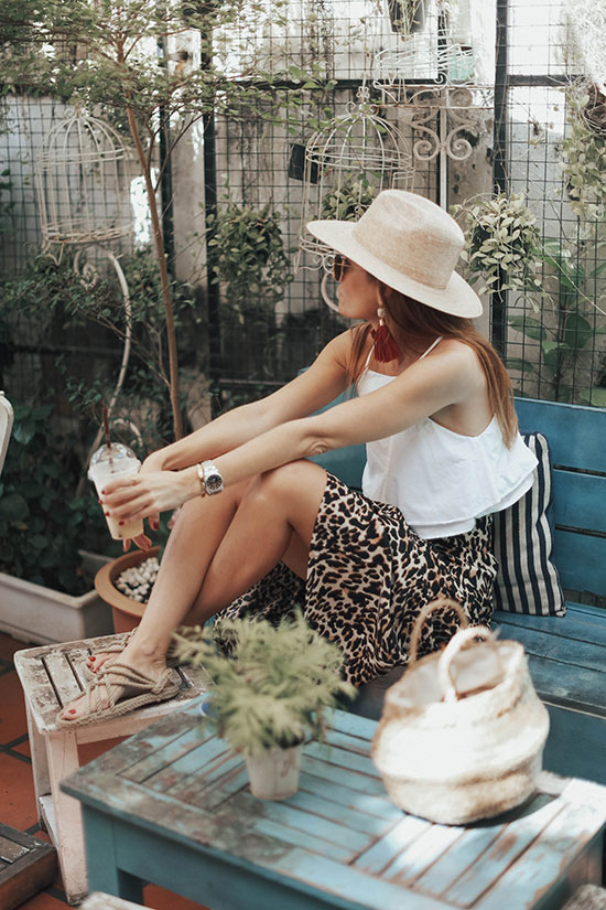 a white linen crop top, a leopard midi skirt, rope sandals, a hat and tassel earrings plus a woven bag