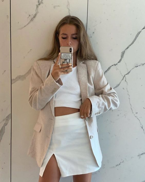 a white linen crop top and a matching A-line mini skirt with a slit, a neutral linen blazer and a necklace to look sexy