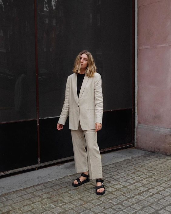 a white linen pantsuit with an oversized blazer, a black t-shirt and black dad sandals for a chic and comfortable summer work look