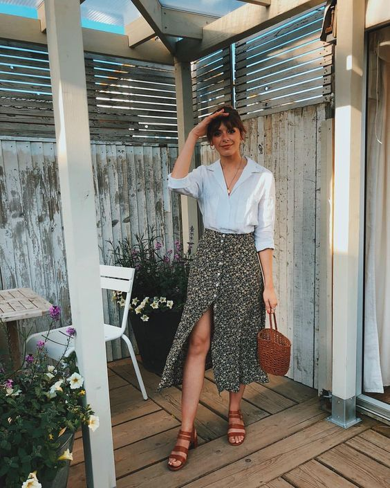 a white linen shirt, a black printed button up midi skirt, brown strappy shoes and a basket bag