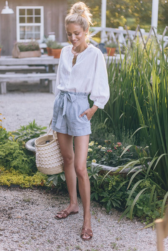 a white linen shirt, blue gingham shorts, brown slippers, a woven bag with lace