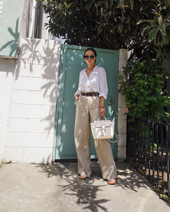 a white linen shirt, neutral linen wideleg pants, a brown belt, heels and a white bag