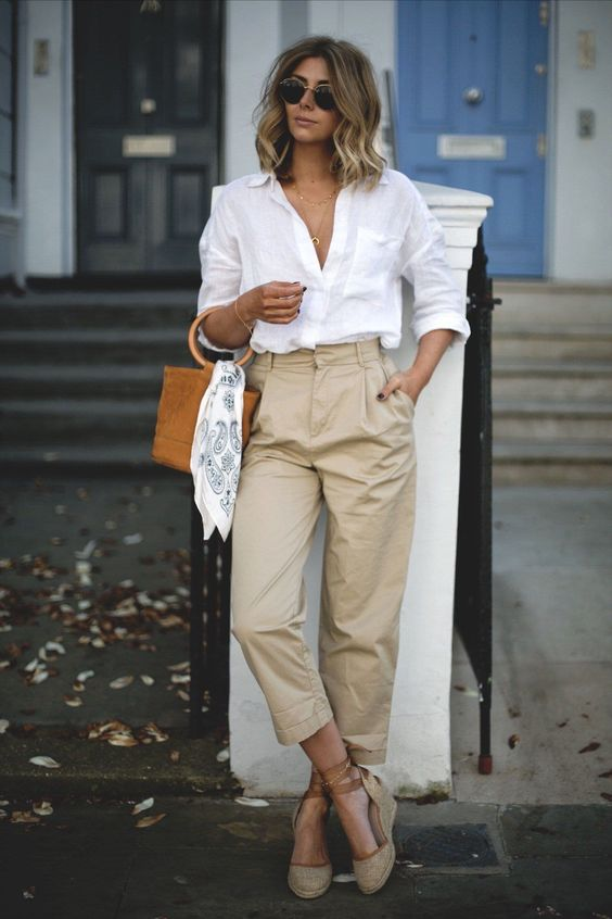 a white linen shirt, tan linen trousers, espadrilles and an amber bucket bag with round handles
