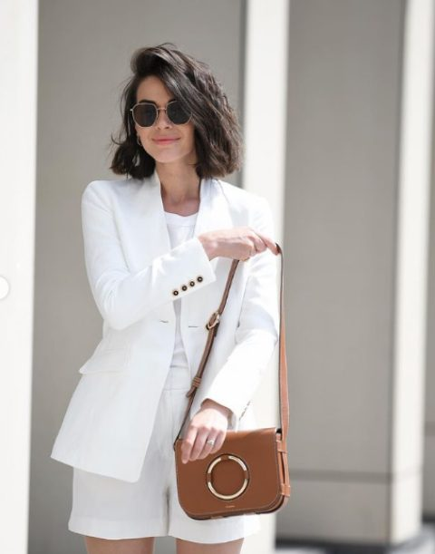 a white linen suit with shorts, a white top and a brown bag for an elegant summer work look