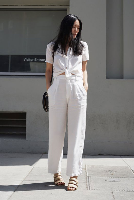 a white linen tied up shirt, white linen pants, nude sandals, a black round bag are a cool minimal look for summer