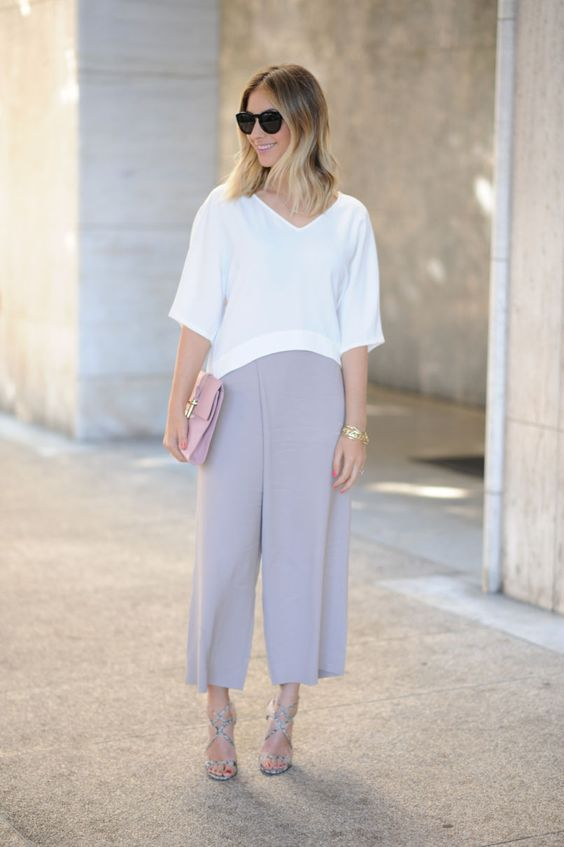 a white loose top with short sleeves, lilac culottes, a pink clutch and colorful lace up shoes