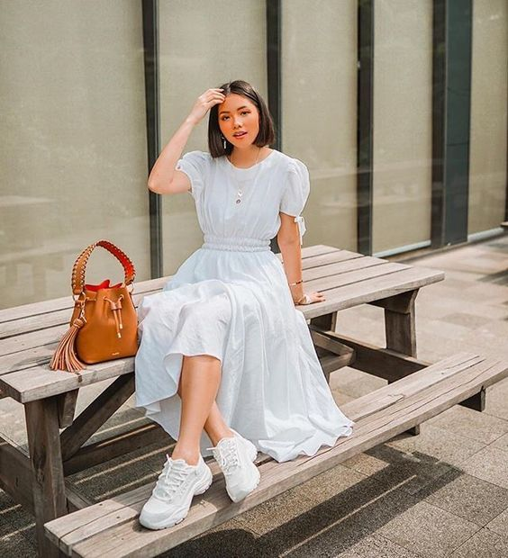 a white midi dress with a high neckline, puff sleeves with bows, white trainers and an amber mini bag
