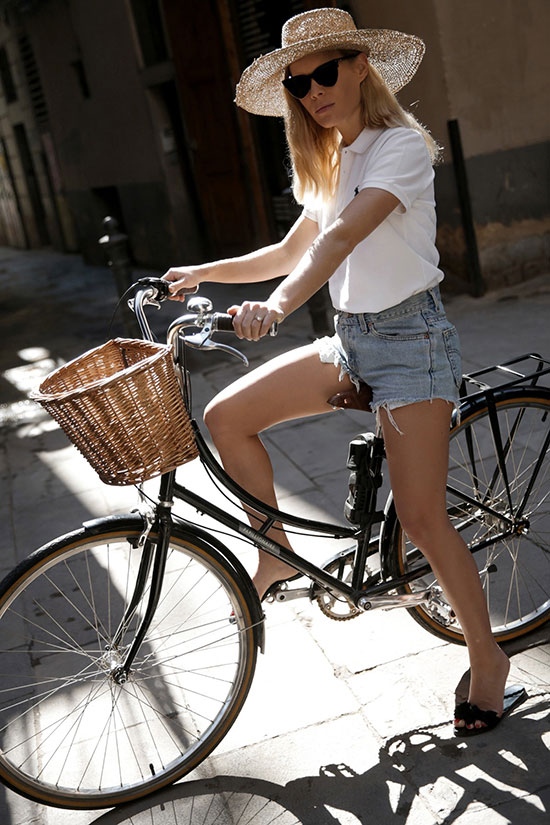a white polo shirt, blue denim shorts, black slippers, a hat compose a cool oufit for hot weather