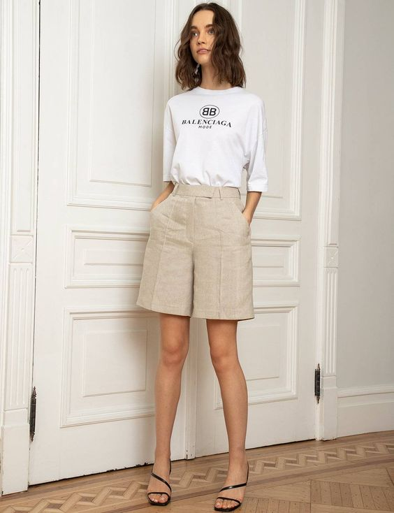 a white printed tee, neutral linen Bermudas, black strappy heels for a neutral and non-boring look