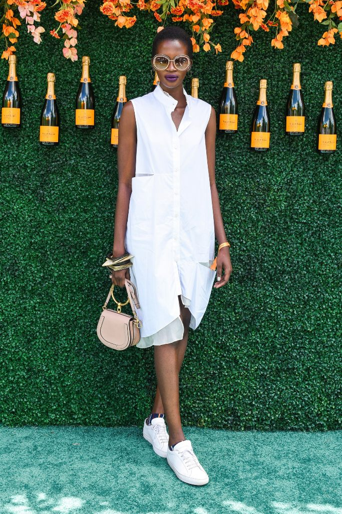 a white sleeveless knee shirtdress with pockets, white sneakers and a blush bag with a ring handle will keep you cool
