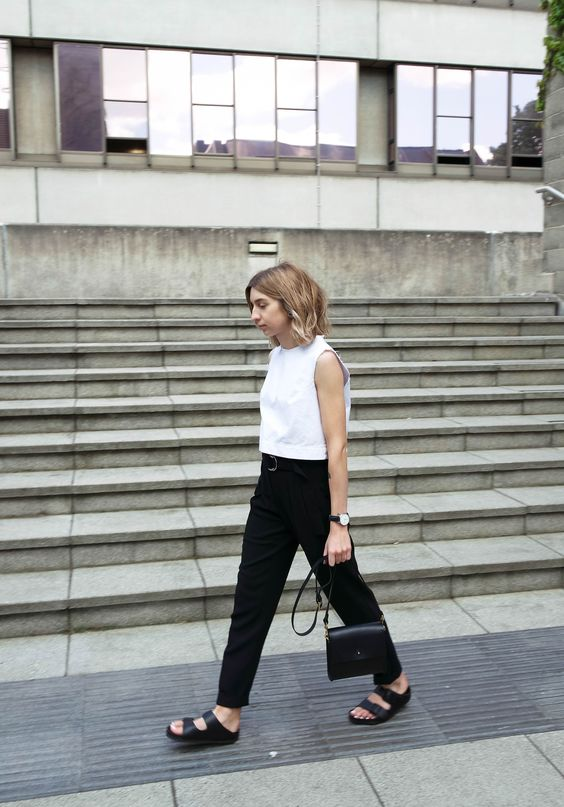 a white sleeveless top, black trousers and a belt, black birkenstocks and a black bag is a cool minimalist look