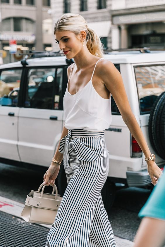 a white spaghetti strap top, high waisted striped flare pants and a small neutral bag for a hot summer day