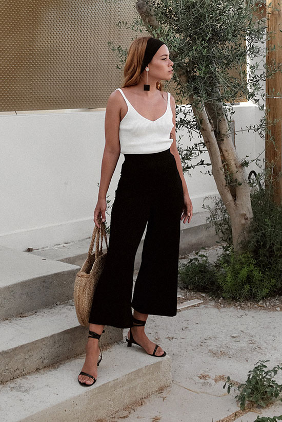 a white strap top, black culottes, black lace up heels, a woven round bag and a headband plus statement earrings