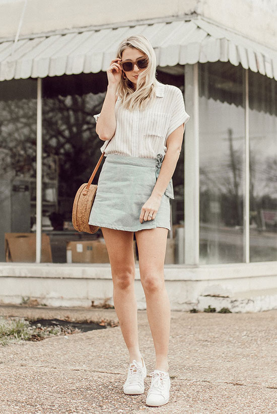 a white striped linen shirt, a blue wrap mini bag, white sneakers and a round woven bag plus statement sunglasses for a chic look