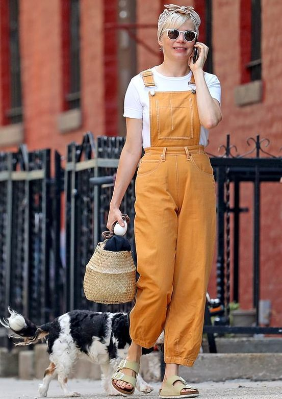 a white t shirt, a sunny yellow overall, grey birkenstocks, a woven bag for a cute summe rlook