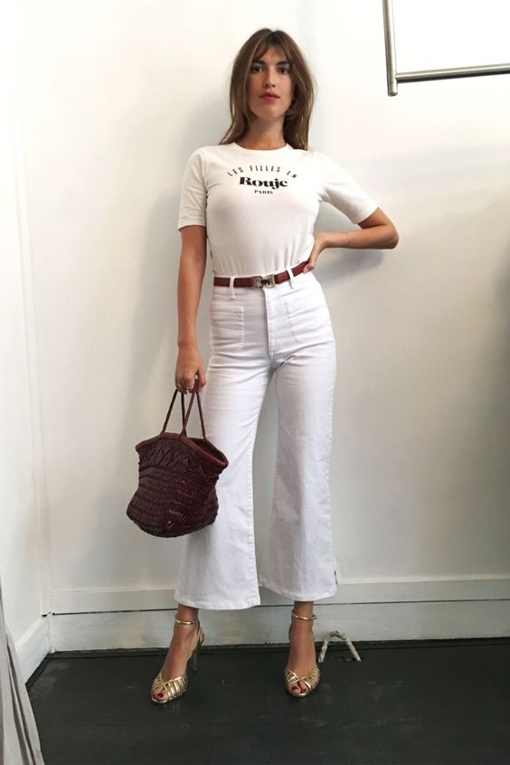 a white t shirt, white jeans, a brown belt, shiny metallic heels and a burgundy bag