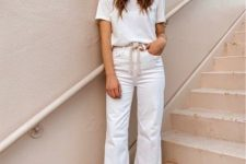a white t-shirt, white jeans with a raw hem, neutral mules, a hat and a woven sash