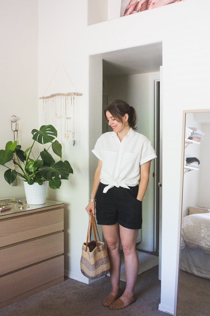 a white tied up shirt, black linen shorts, brown slippers, a striped bag are all you need to feel comfortable