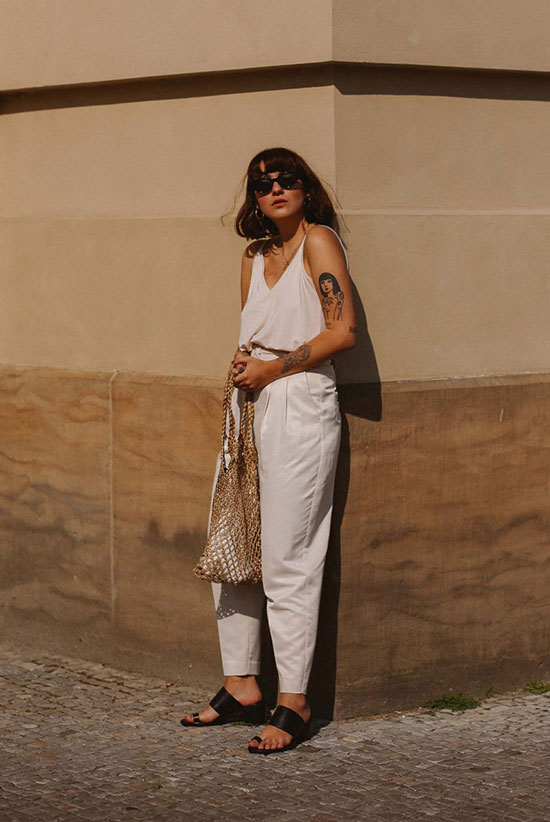 a white top, white trousers with pockets, black block heels, a woven bag and statement earrings