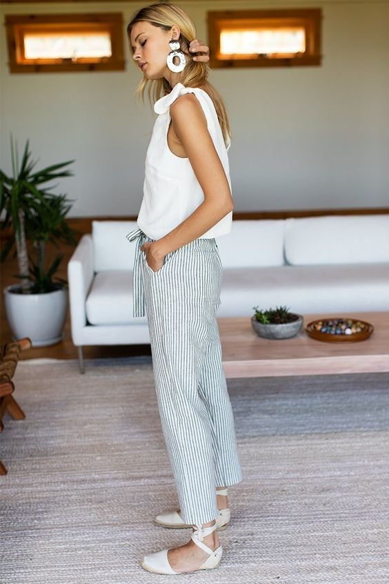 a white top with bows on shoulders, cropped pinstripe pants, white espadrilles and statement earrings