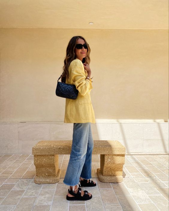 a yellow linen blazer, blue jeans, black dad sandals and a black bag for a bright and cheerful sumemr work look