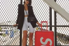 an airport look with a white crop top and biker shorts, a black oversized blazer, neutral sneakers and a black bag