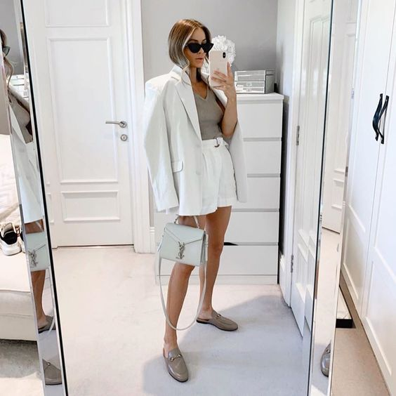 an elegant and chic summer work look with a grey top and a white linen short suit, grey slipper mules and a light grey bag is ultimate