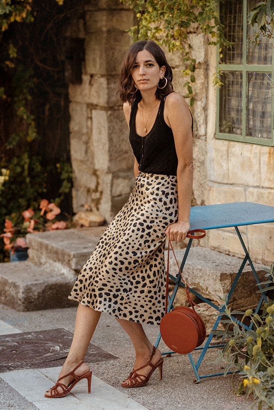 an elegant date look with a black top, a leopard print midi, brown heels and a brown round bag plus statement earrings