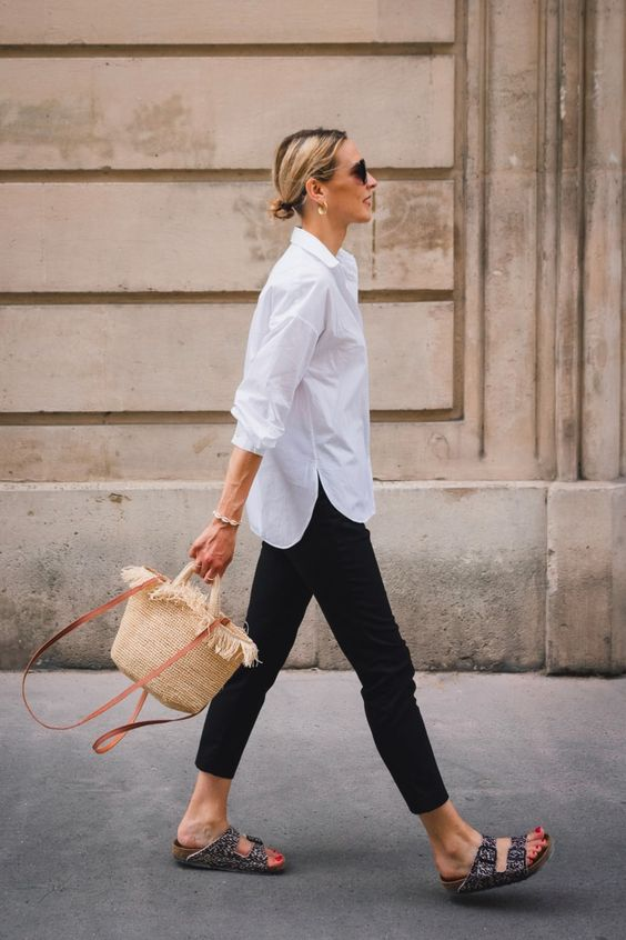 an elegant summer work look with a white shirt, black jeans, printed birkenstocks and a woven bag is easy and chic
