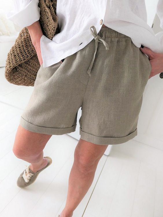 an everyday look with a white linen shirt, green linen Bermudas, green sneakers and a woven bag