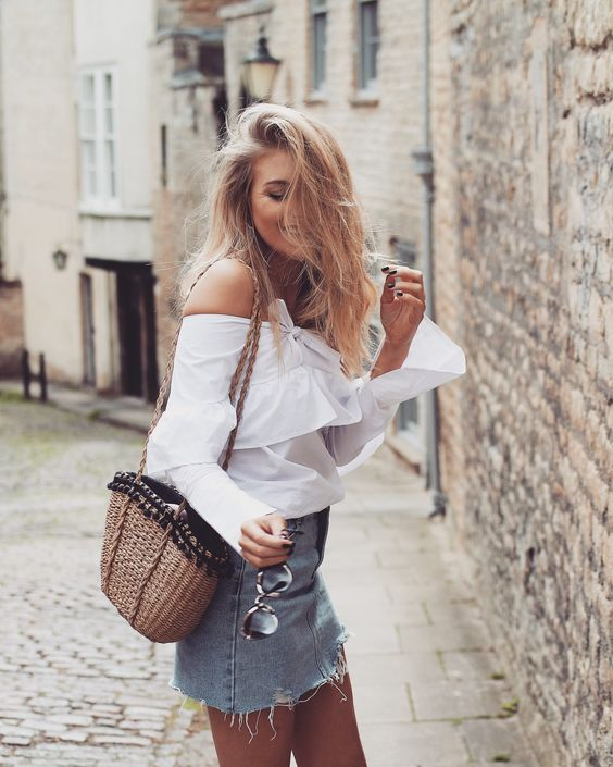 an off the shoulder white blouse with long bell sleeves, a blue A-line denim mini and a woven bag for summer