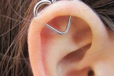 an orbital piercing done with a large heart earring is a creative idea to add a bit of cuteness to your look