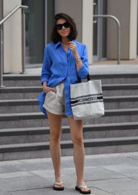 an oversized bold blue linen shirt, neutral linen shorts, flipflops and a striped shooper bag